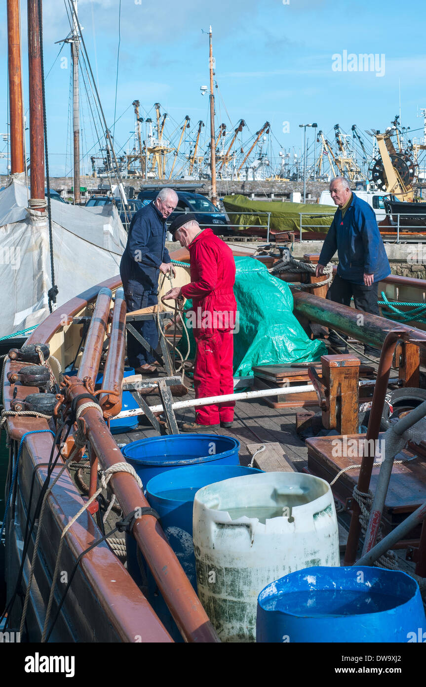 sailors repairing old boat in brixham,devon,fishing fleet docked at Brixham Harbour,Architecture,Brixham,Building Stock Photo