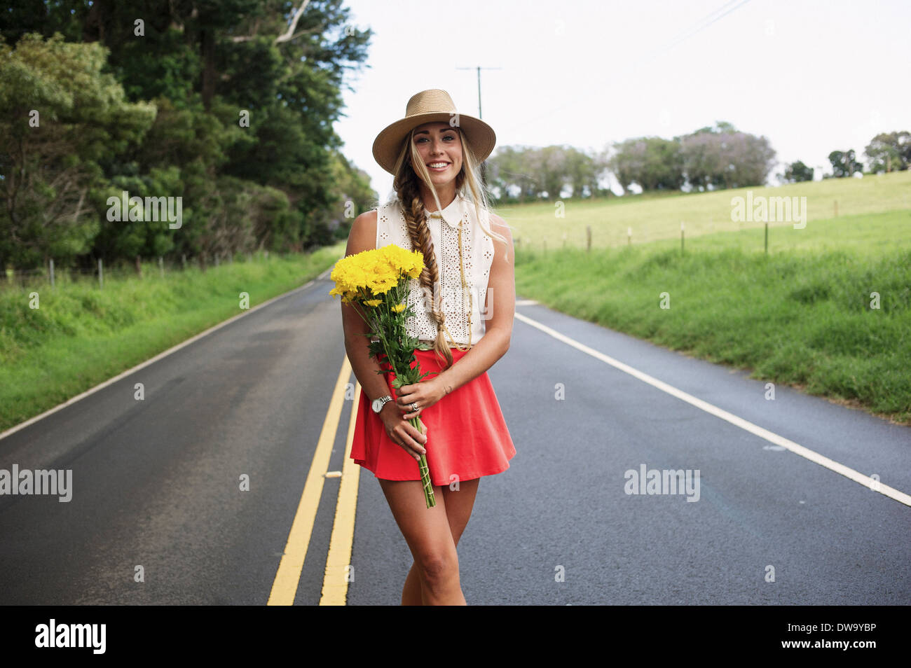 Young woman with flowers on road - Stock Image