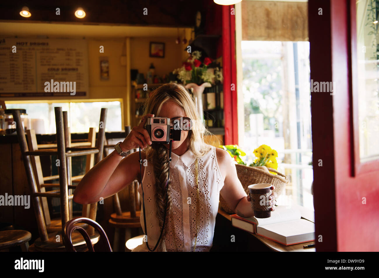 Young woman taking photograph in cafe - Stock Image