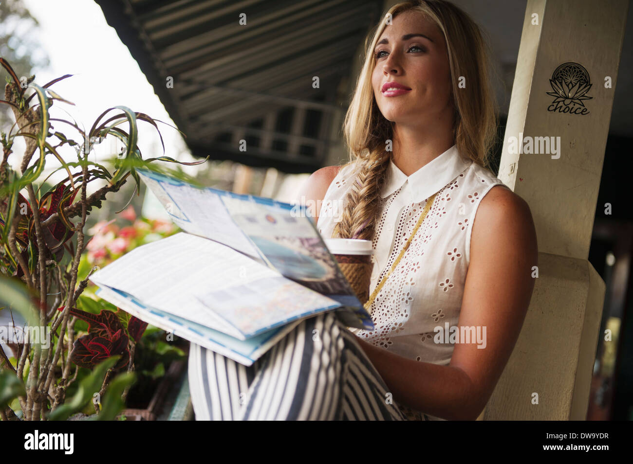 Young woman with map daydreaming - Stock Image