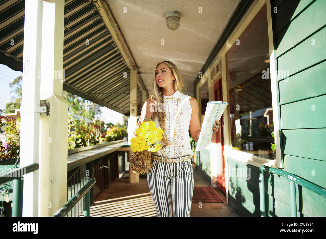 Young woman with map in verandah - Stock Image