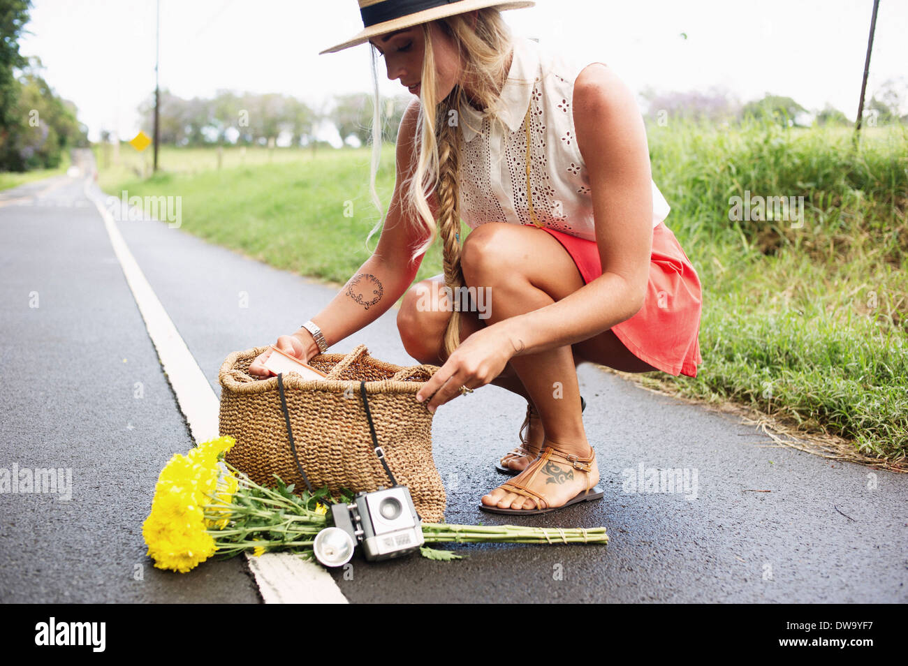 Young woman squatting on roadside - Stock Image