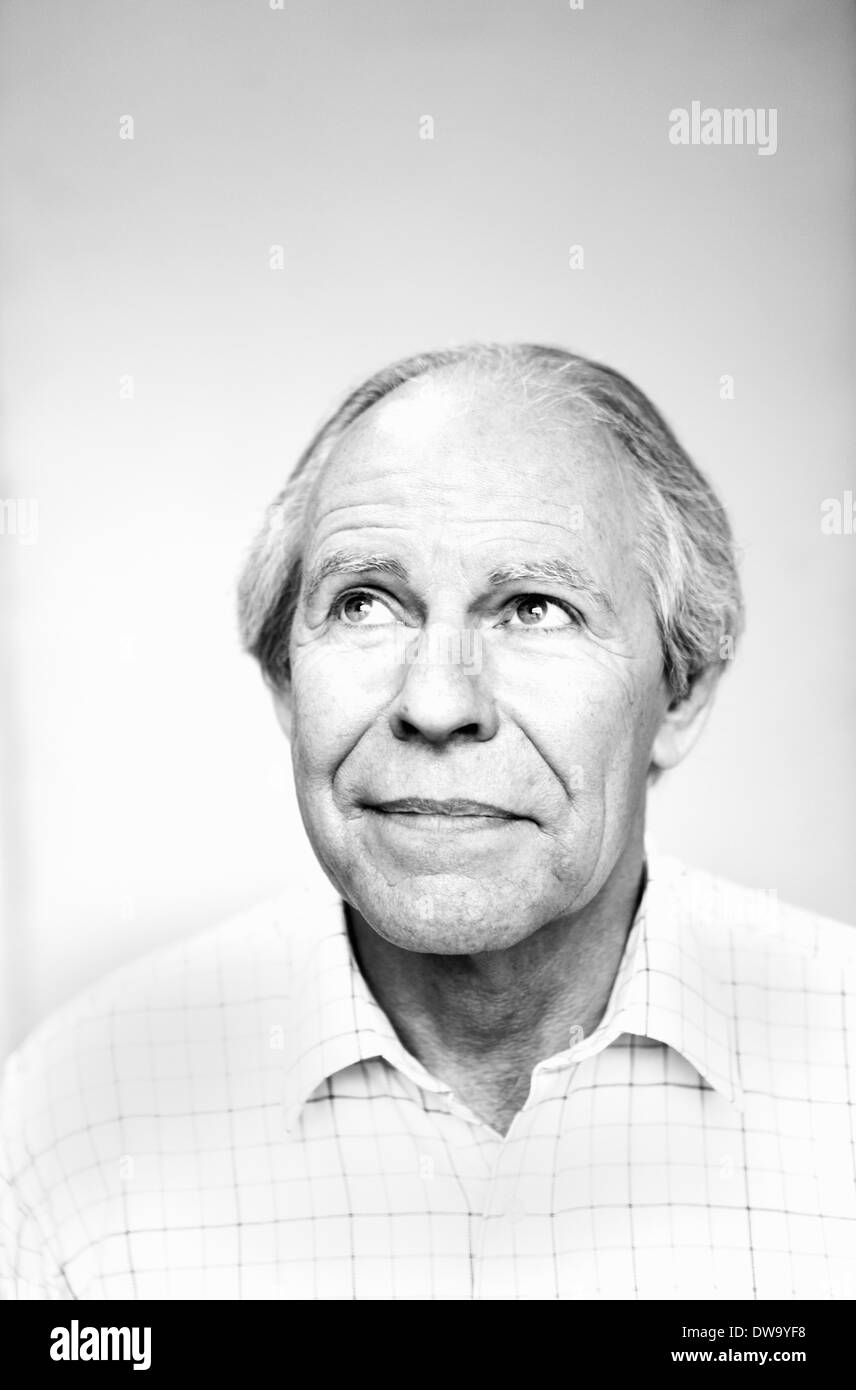 Black and white studio portrait of senior man looking up - Stock Image