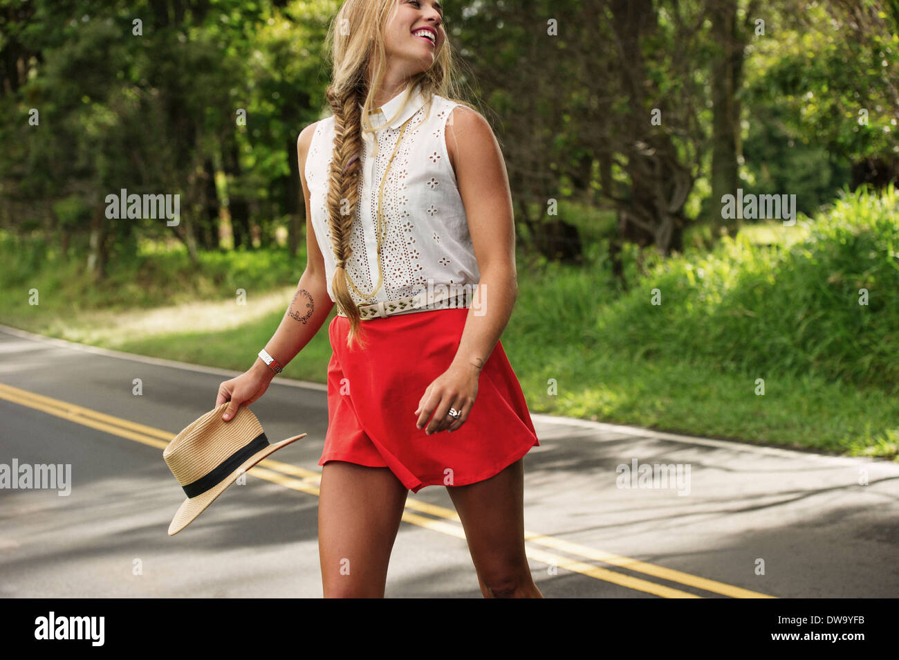 Young woman with hat crossing road - Stock Image