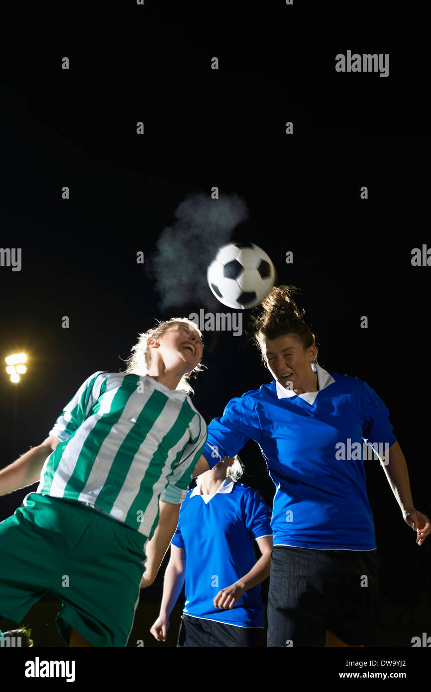 Female soccer players hitting ball with head - Stock Image