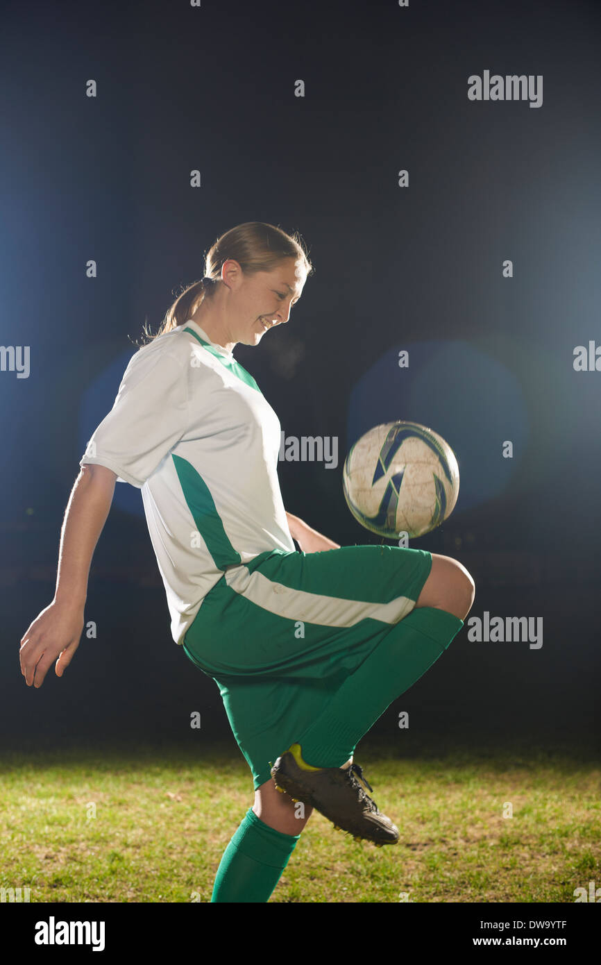 Female soccer player bouncing ball on knee - Stock Image