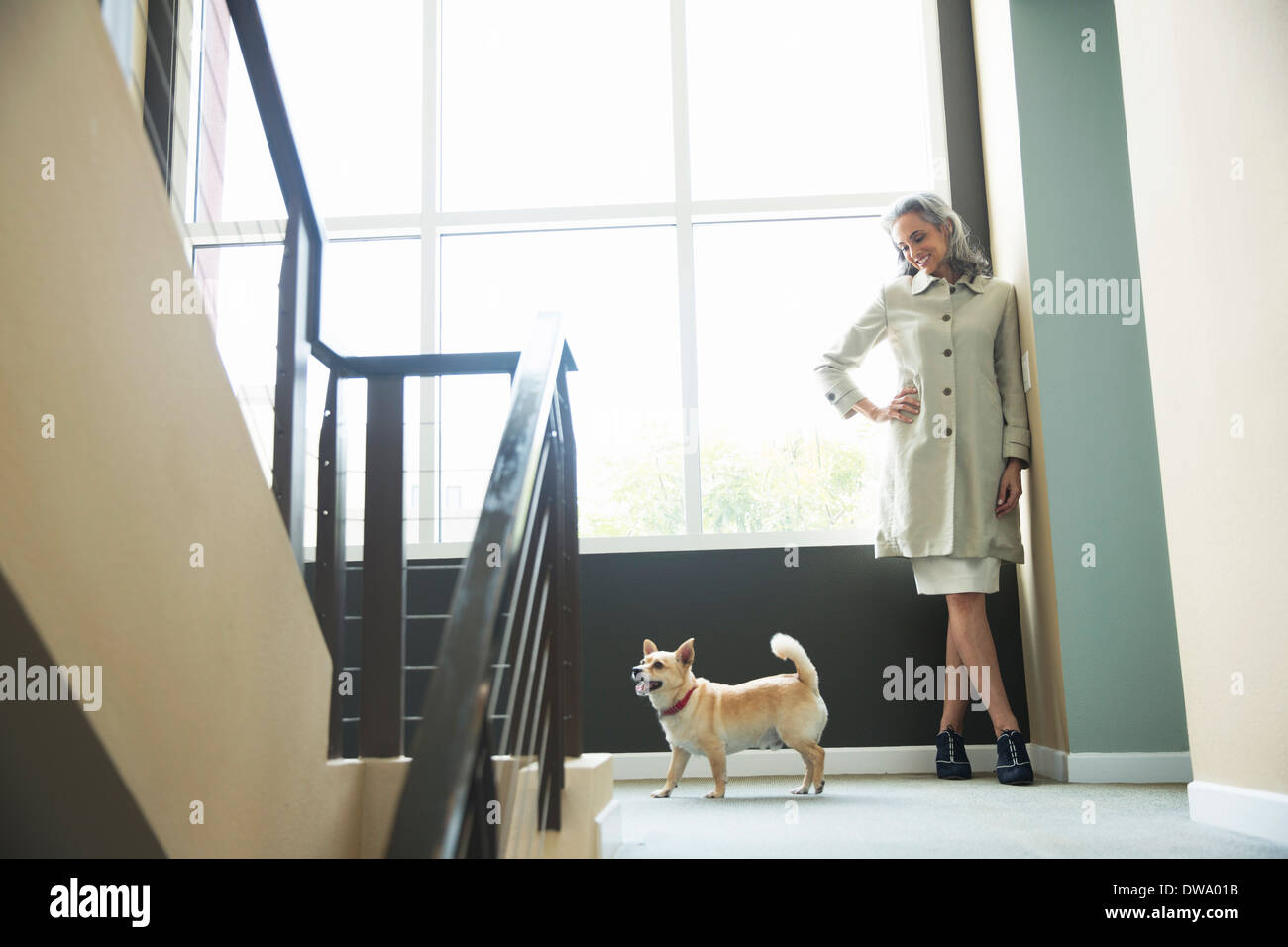 Mature woman and pet dog on stairwell Stock Photo