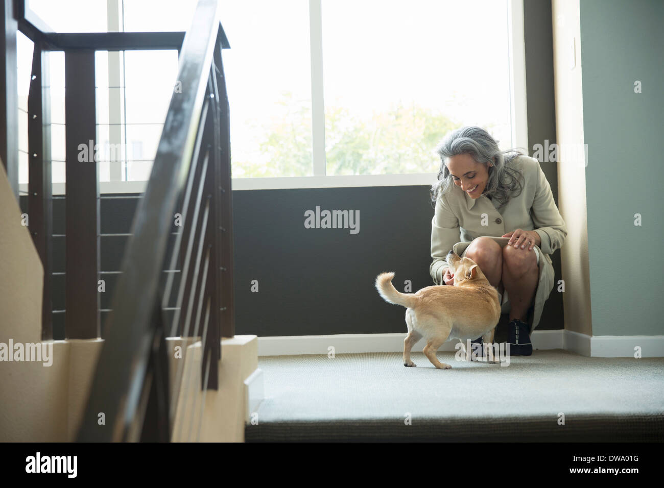 Mature woman petting her dog on stairwell - Stock Image