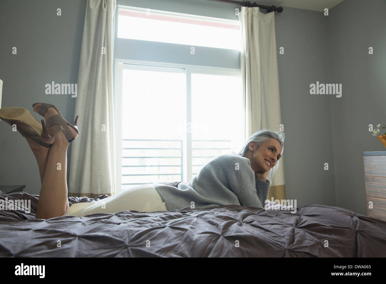 Mature woman relaxing on luxury bed - Stock Image
