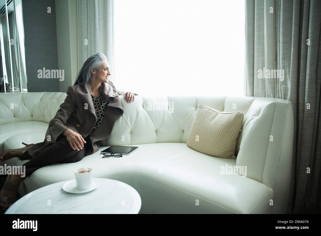 Portrait of mature woman reclining on white luxury sofa - Stock Image