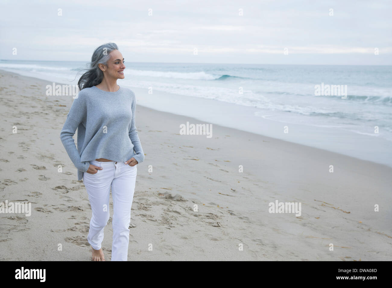 Mature woman walking on beach, Los Angeles, California, USA - Stock Image