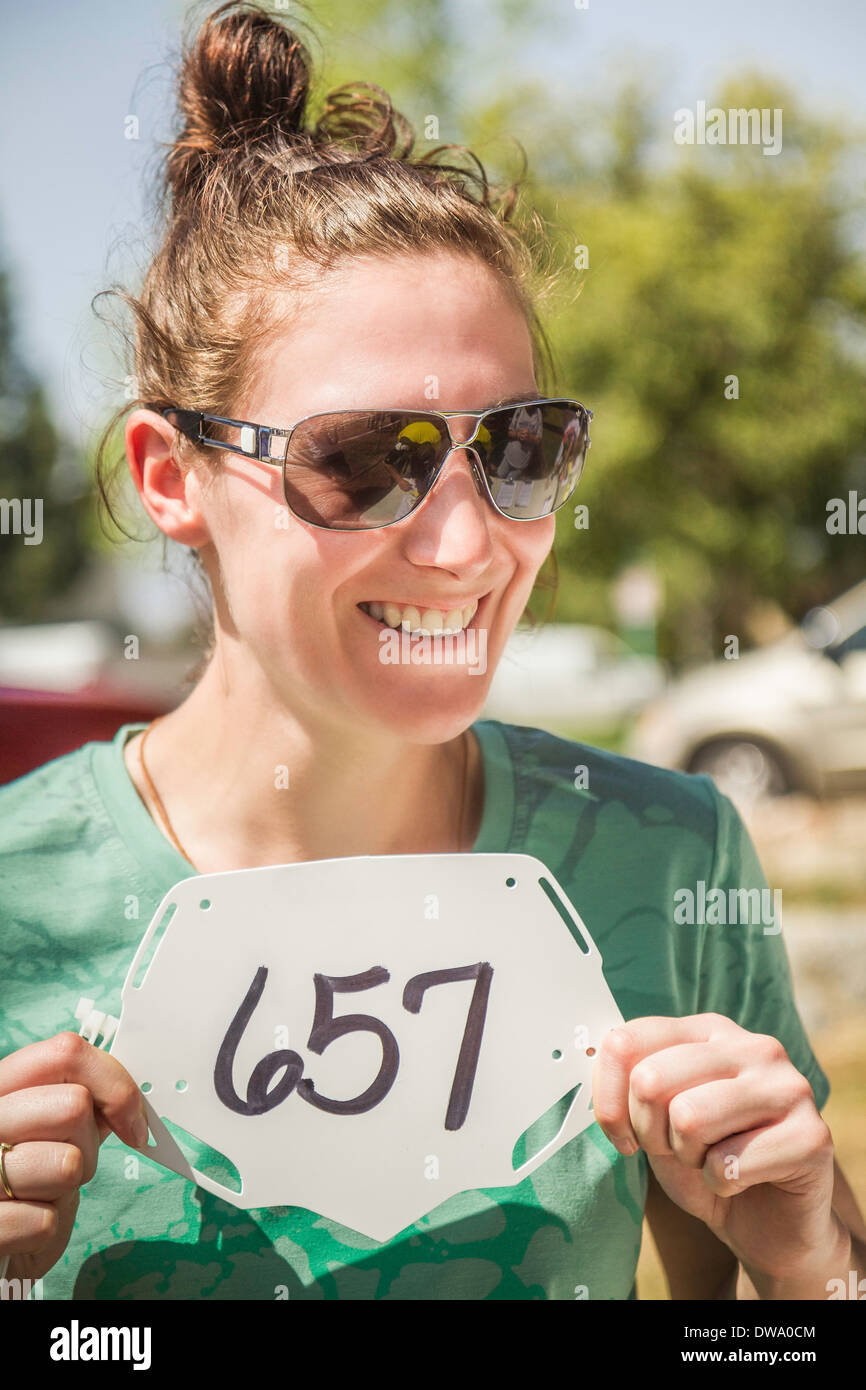 Young female mountain biker holding up race number - Stock Image