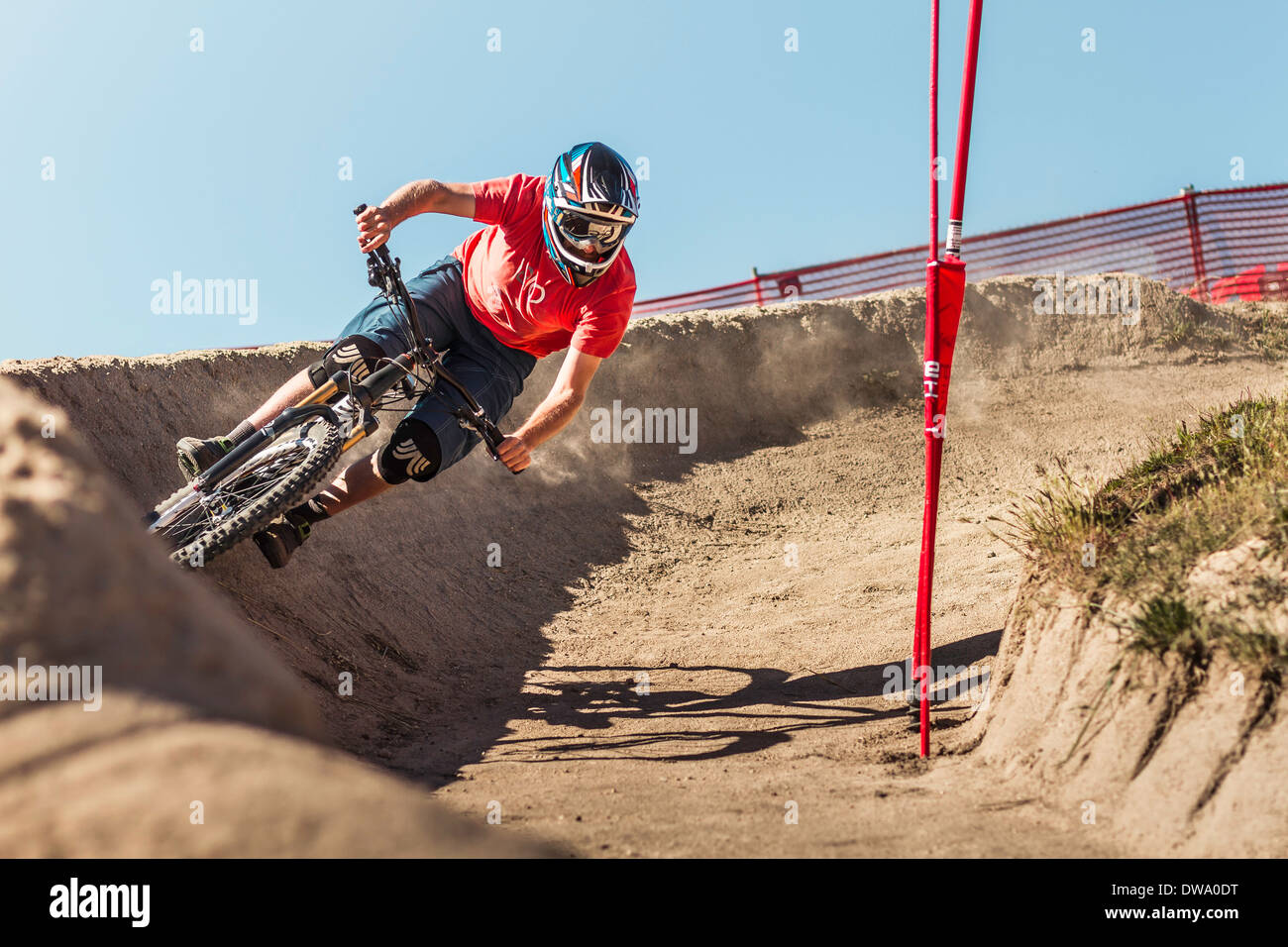 Young male mountainbiker racing in Sea Otter Classic Mountainbike Festival on Laguna Seca Raceway near Monterey - Stock Image