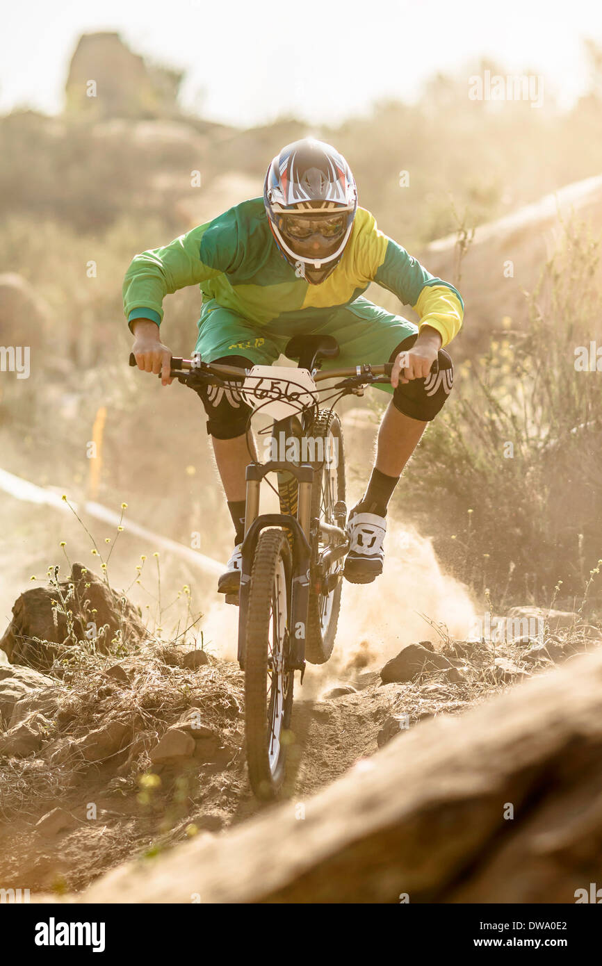 Male mountain biker racing on dusty track, Fontana, California, USA - Stock Image