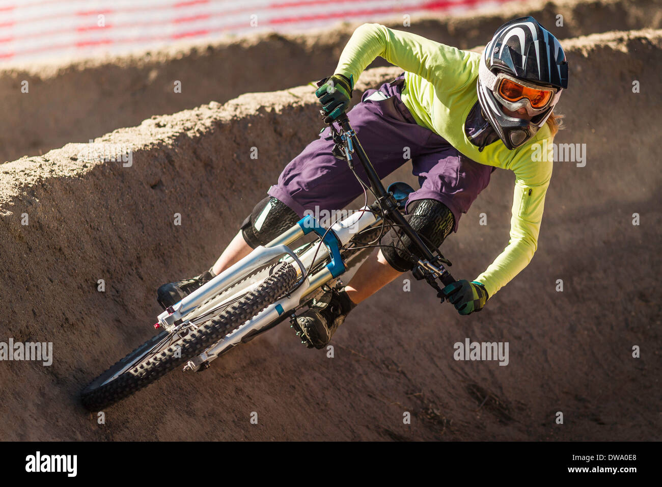 Young female mountainbiker racing in Sea Otter Classic Mountainbike Festival on Laguna Seca Raceway near Monterey - Stock Image