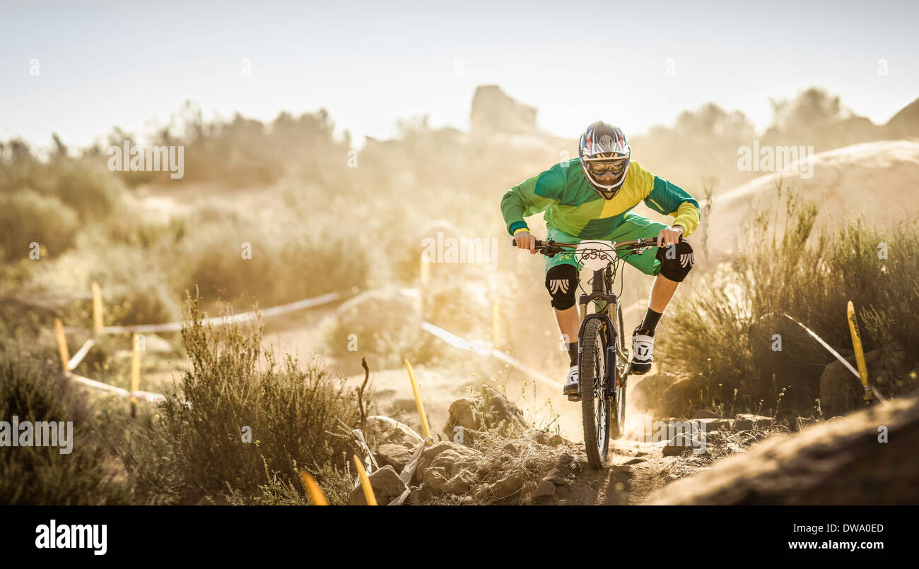 Male mountain biker racing on dusty dirt track, Fontana, California, USA - Stock Image