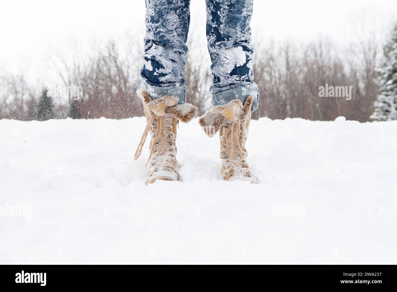 Close up of mid adult womans legs covered in snow Stock Photo