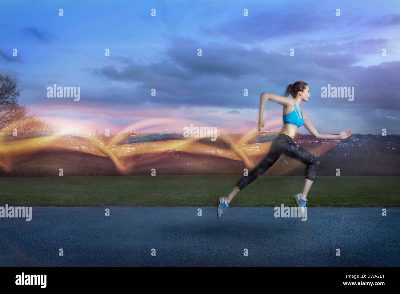 Young woman running with light trails - Stock Image