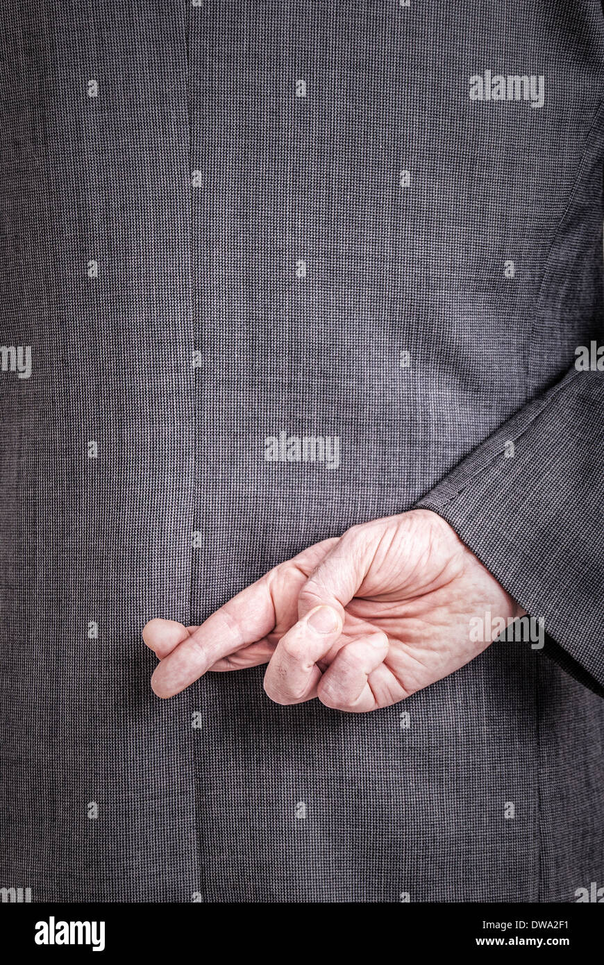 A conceptial image of a business man with his fingers crossed behind his back. - Stock Image