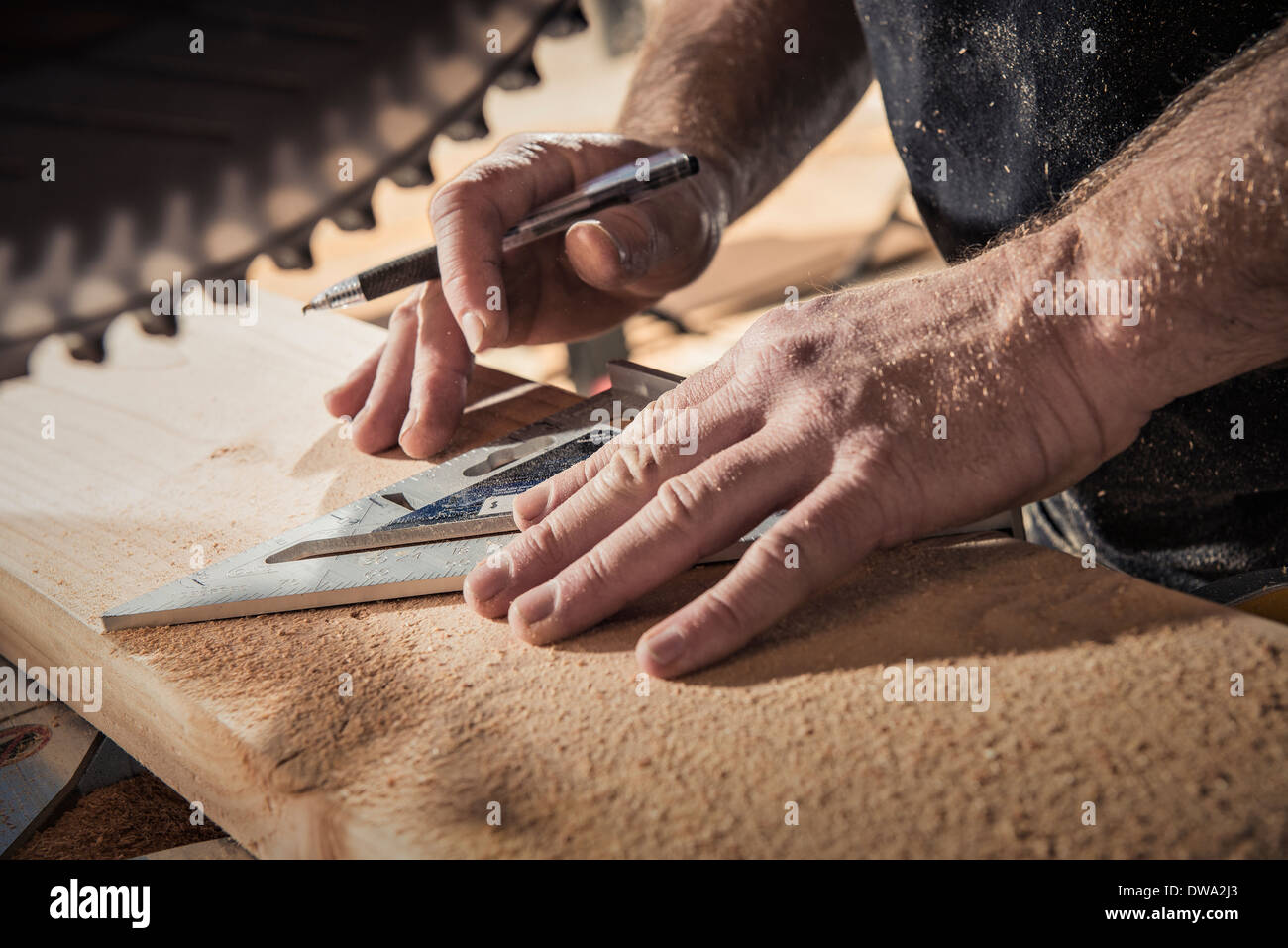 Close up of male carpenter with set square in workshop - Stock Image