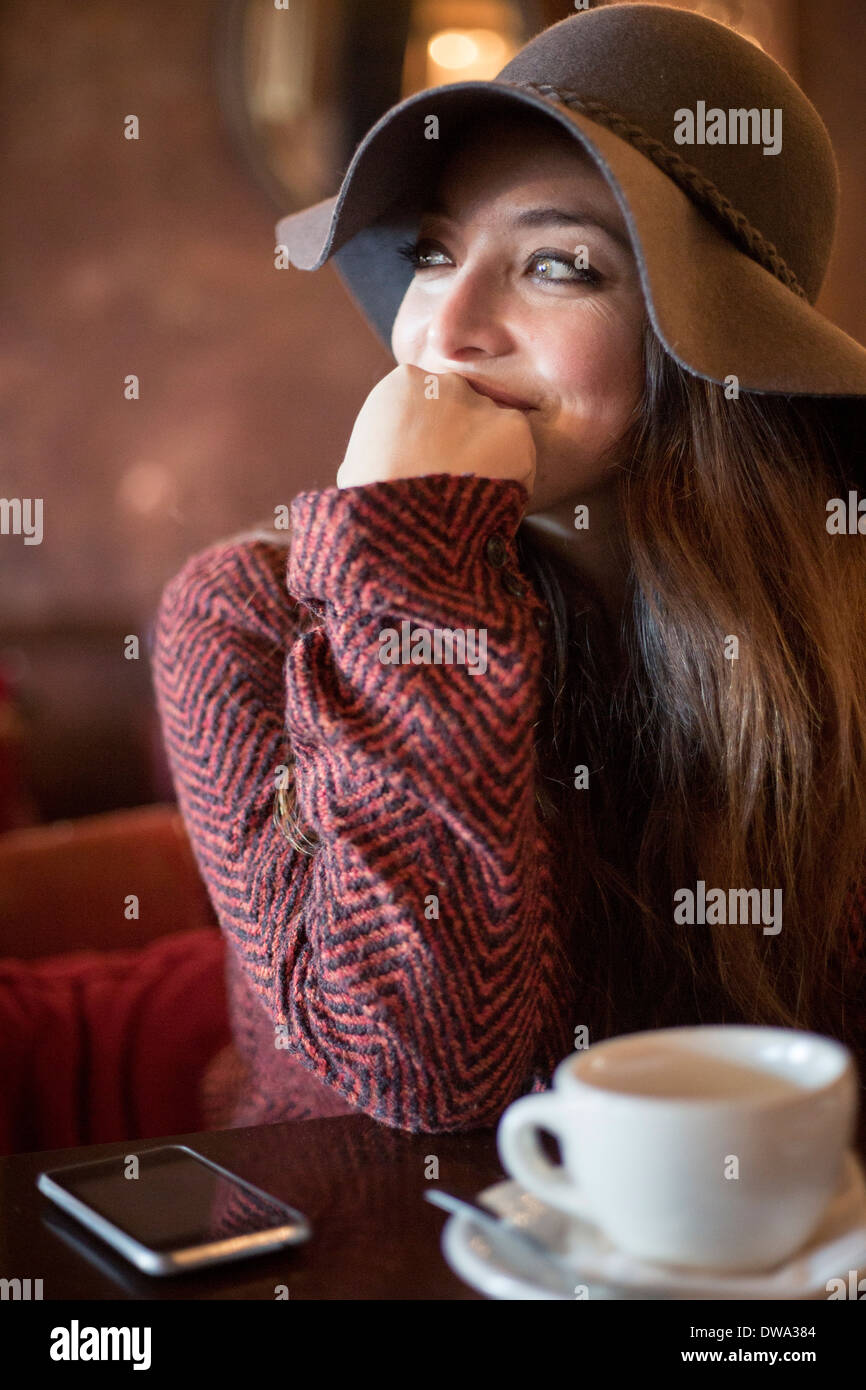 Portrait of young woman wearing hat leaning on elbow - Stock Image
