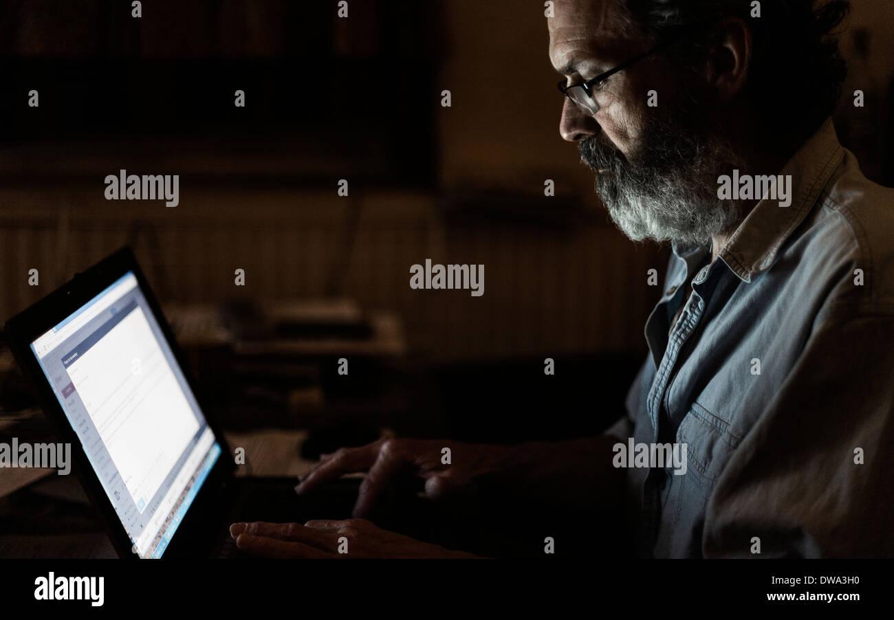 Mature man using laptop - Stock Image