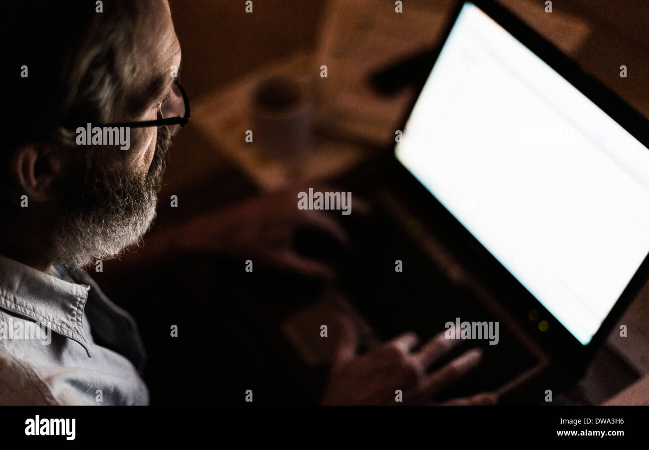 Mature man using laptop with blank screen - Stock Image