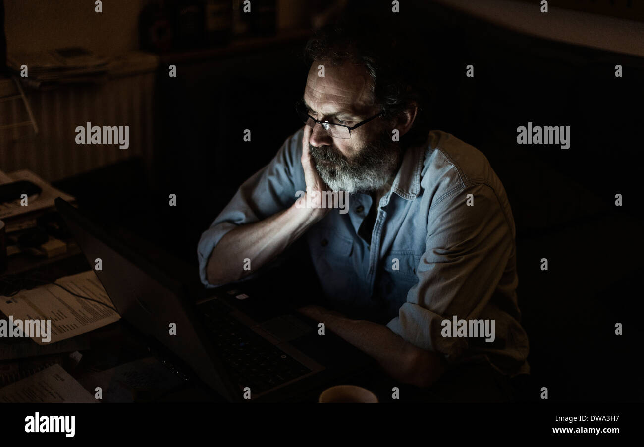 Mature man working late - Stock Image