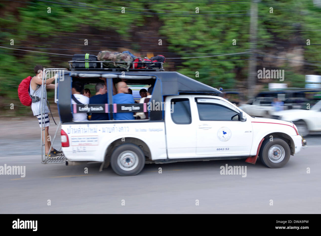 Tourists riding on the bumper of a crowded shared taxi, also known as a songthaew, on Koh Chang Island, Thailand. - Stock Image