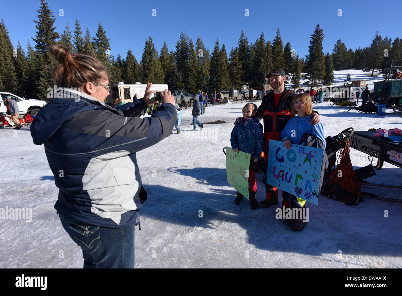Woman taking picture of a musher and young boosters at the Eagle Cap Extreme dog sled race in Oregon's Wallowa Mountains. - Stock Image