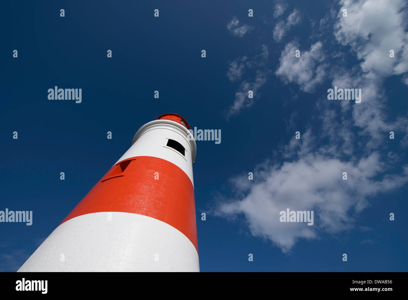 A red and white lighthouse, photographed from a low angle, stretches into a deep blu sky with white clouds and text Stock Photo