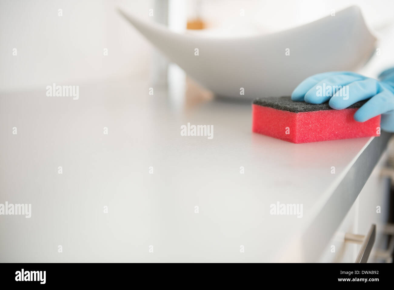 Closeup on young woman cleaning desk in bathroom - Stock Image