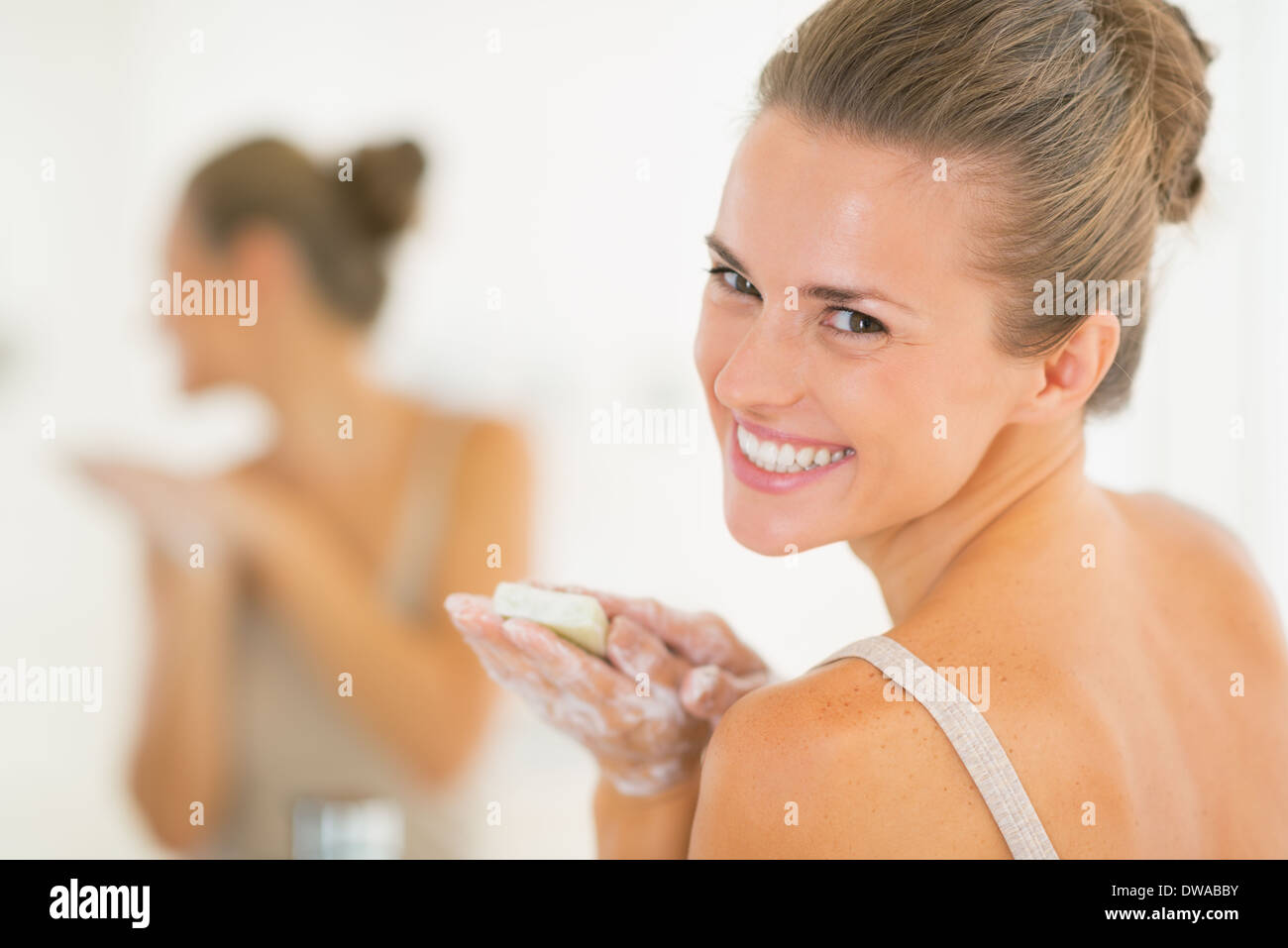 Portrait of smiling young woman washing hands with soap - Stock Image