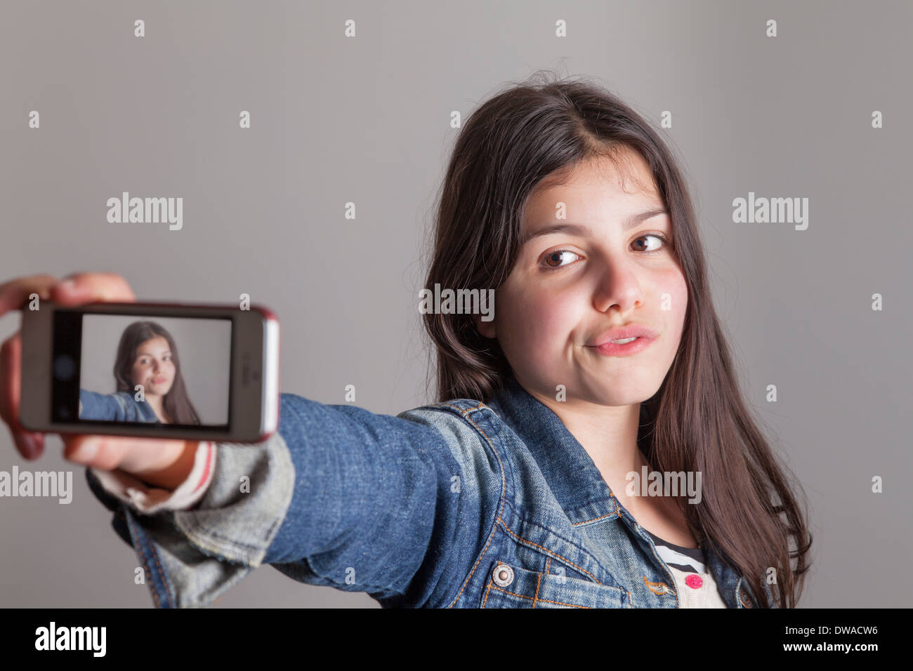 Teenage girl takes a selfie on camera phone - Stock Image