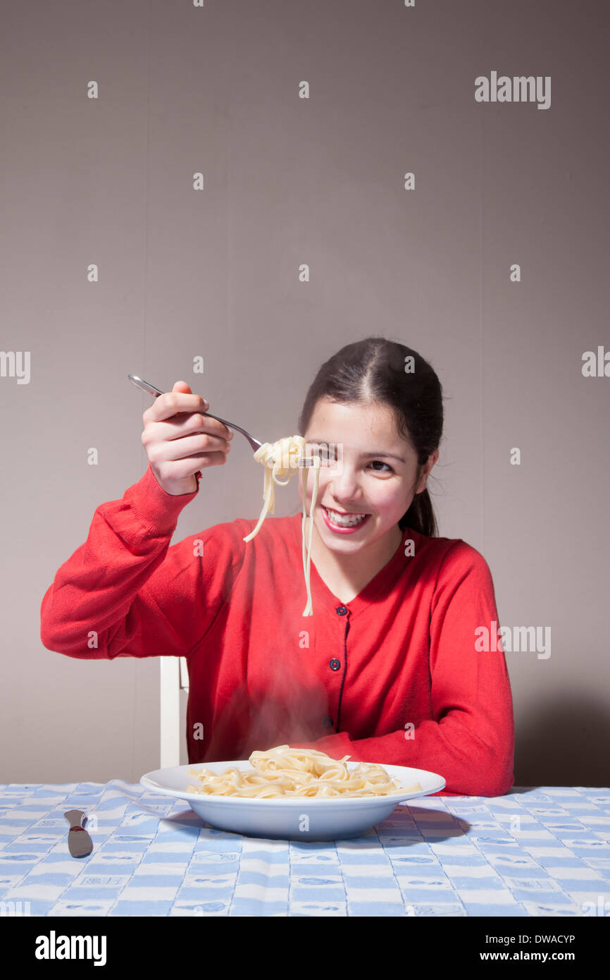 Teenage girl eating pasta - Stock Image