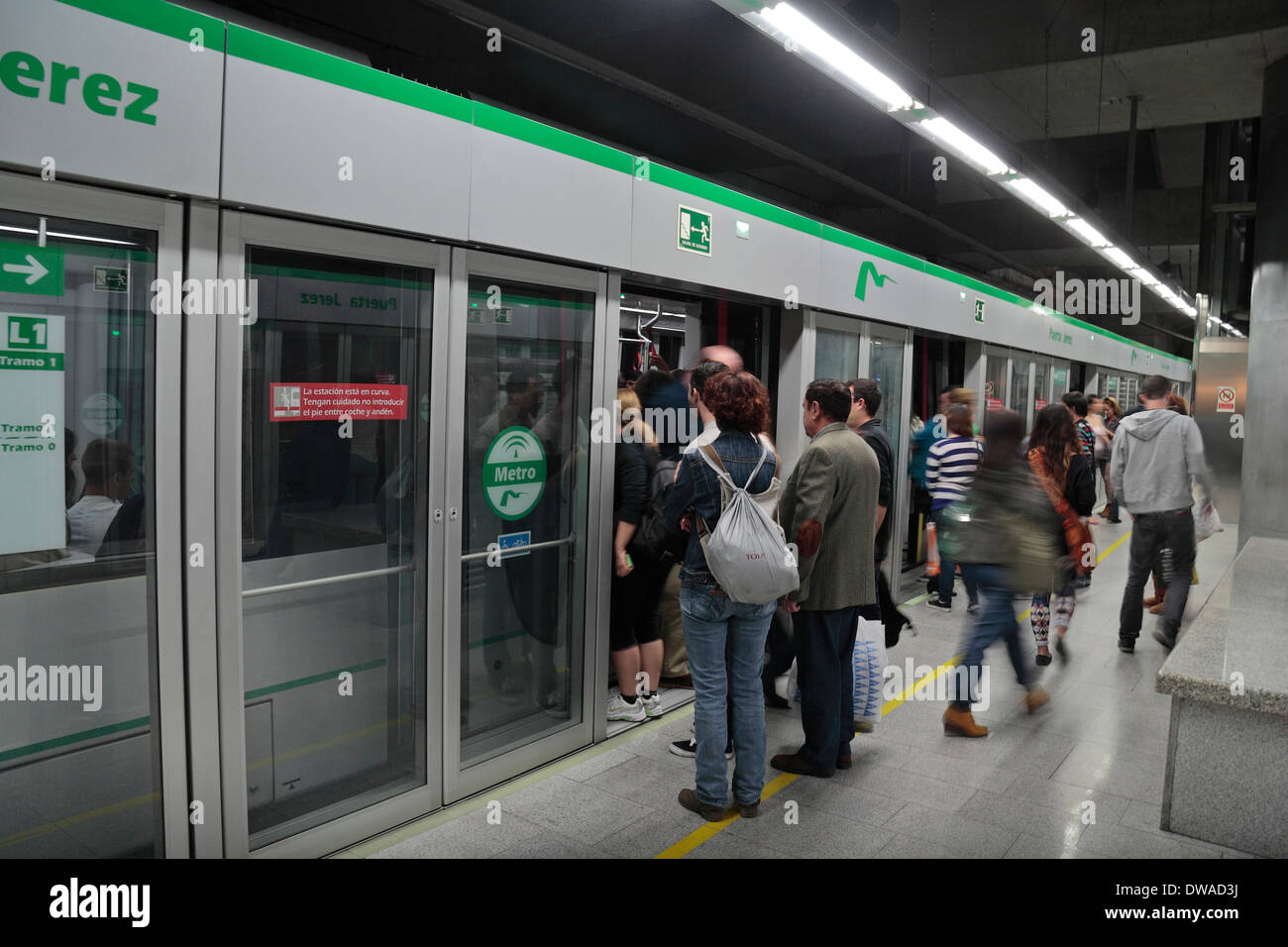 Typical enclosed Metro train platform with a train in the station, Puerta Jerez station, Seville, Spain. - Stock Image