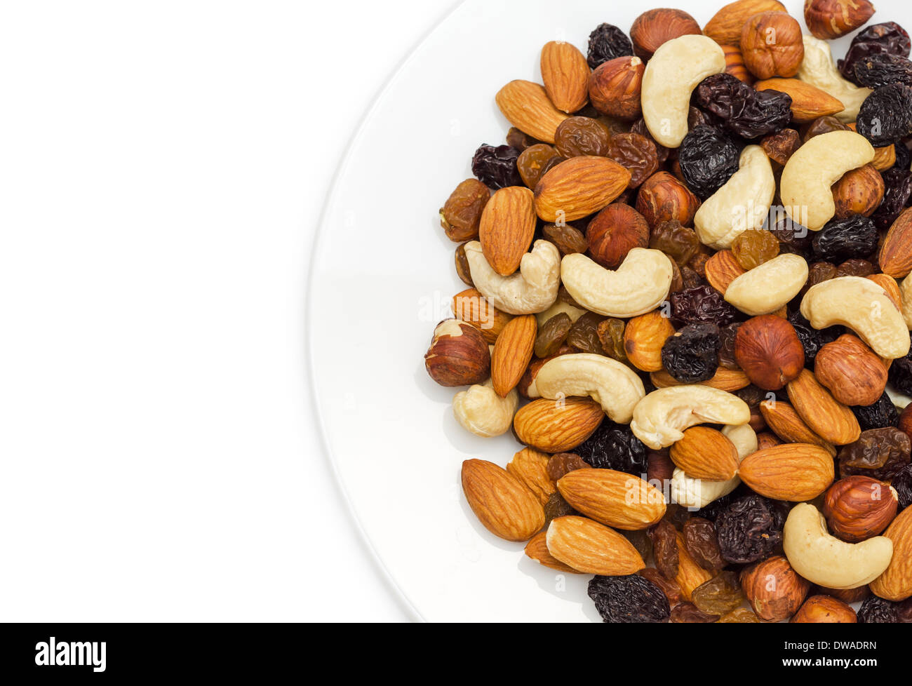 Mixed nuts and dry fruits in plate isolated on white background close-up - Stock Image