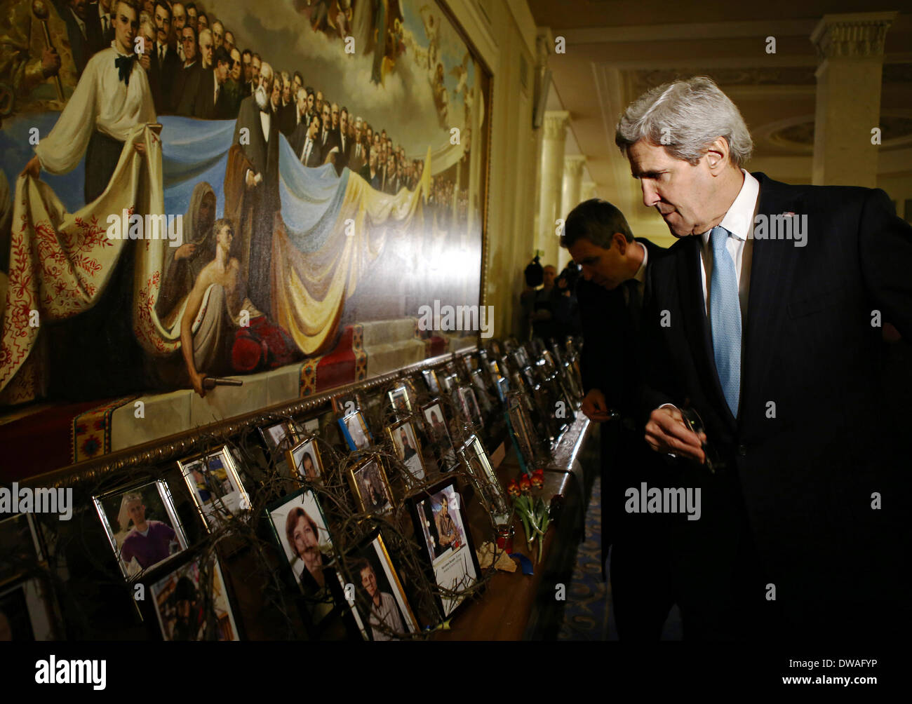 US Secretary of State John Kerry looks at the photos of those killed at Maidan during anti-government protests at the Verkhovna Rada March 4, 2014 in Kiev, Ukraine. In a demonstration of support for Ukraine's fledgling government Kerry offered a $1 billion in American loan guarantee and pledges of technical assistance. - Stock Image