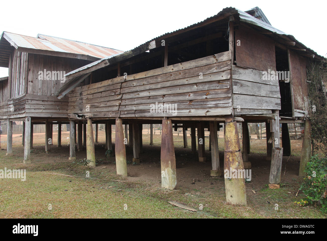 House built in rural Laos using old bombs for supports - Stock Image