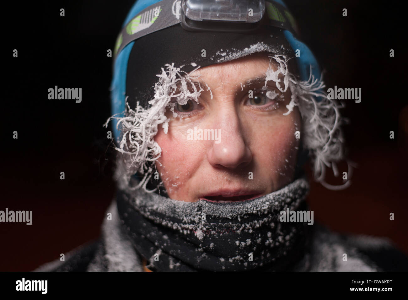 Night time portrait of an outdoors woman with frost on her face, hair and eyelashes - Stock Image