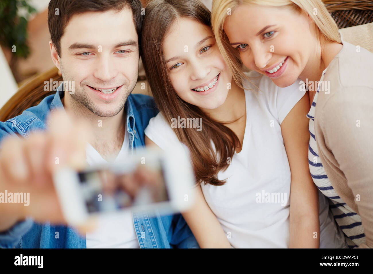 Young man holding cellular phone with happy daughter and wife near by - Stock Image