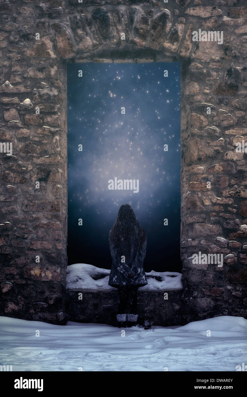 a girl is standing in front of a window of an old castle in the snow - Stock Image