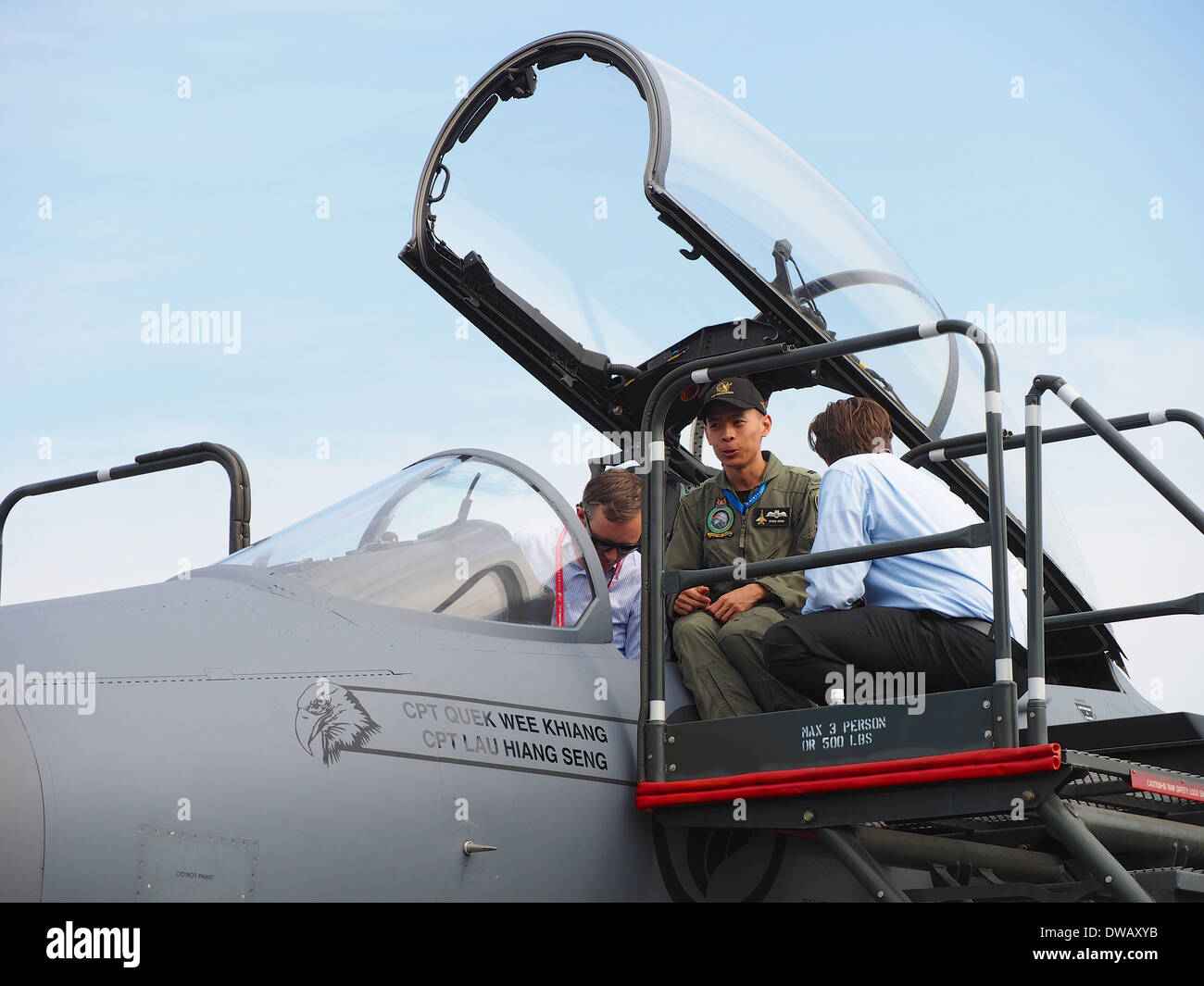 An RSAF personnel explaining the cockpit of the F-16 Fighting Falcons to visitors at the 2014 Singapore Airshow - Stock Image
