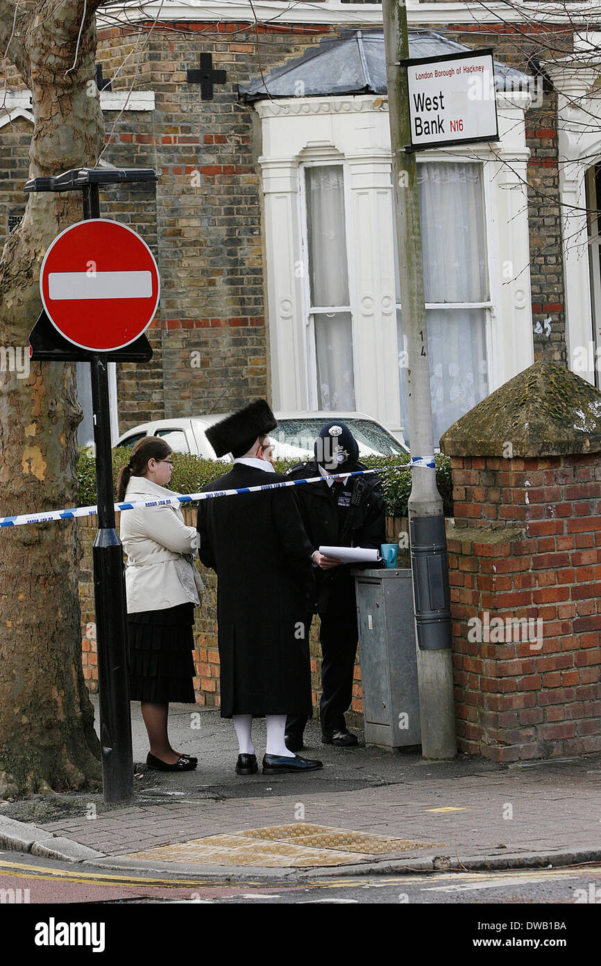 policeman questions local residents at the scene of a 17 year old victim stabbed to death Near Mannor Park North London - Stock Image