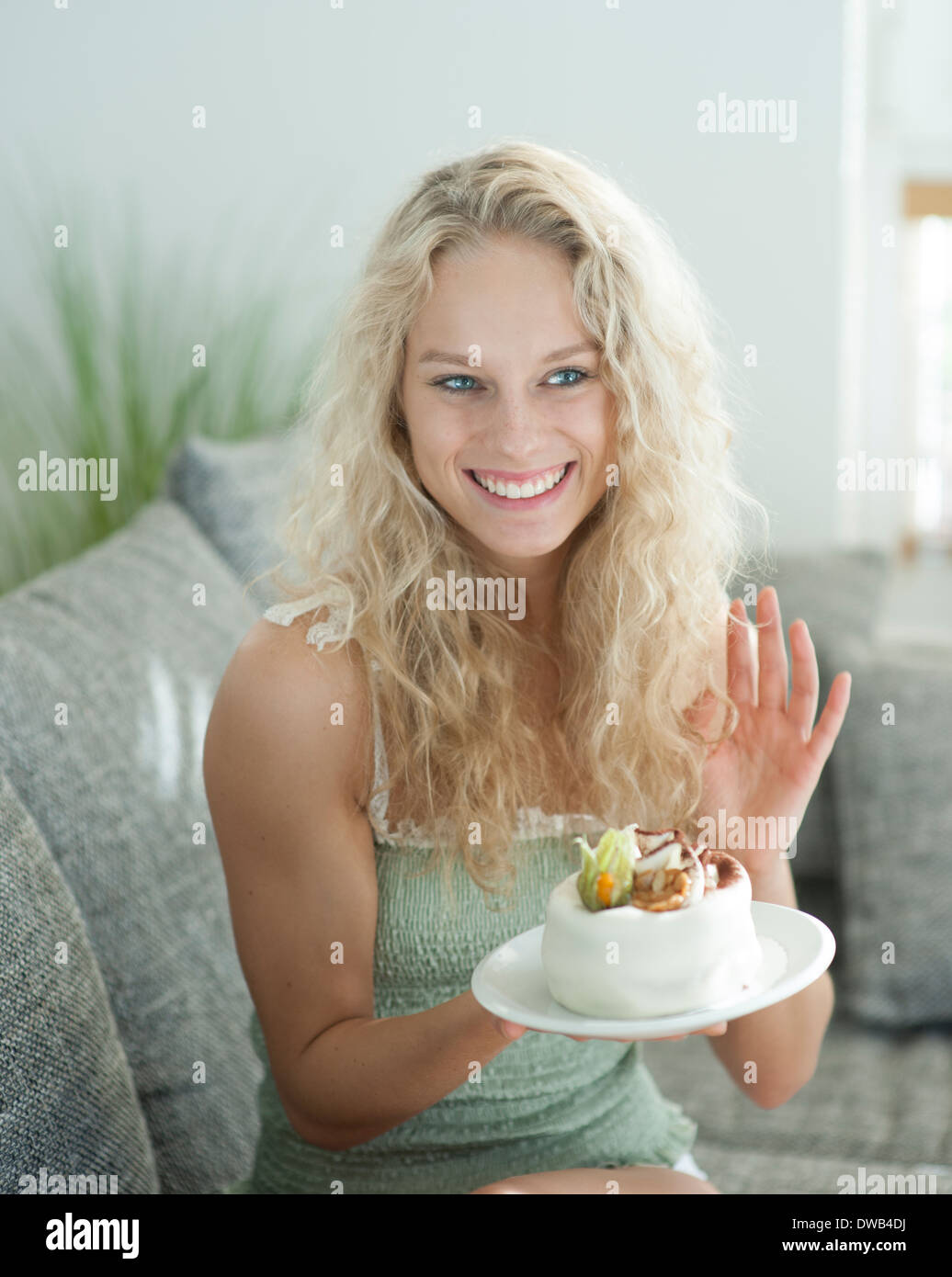 Happy woman gesturing while holding cake in house - Stock Image