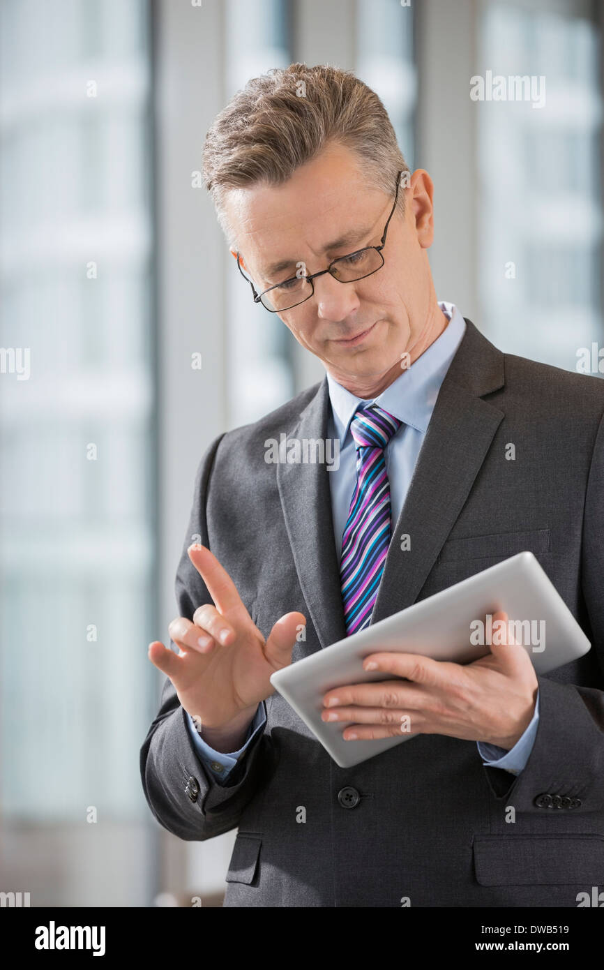 Businessman gesturing while using digital tablet in office - Stock Image