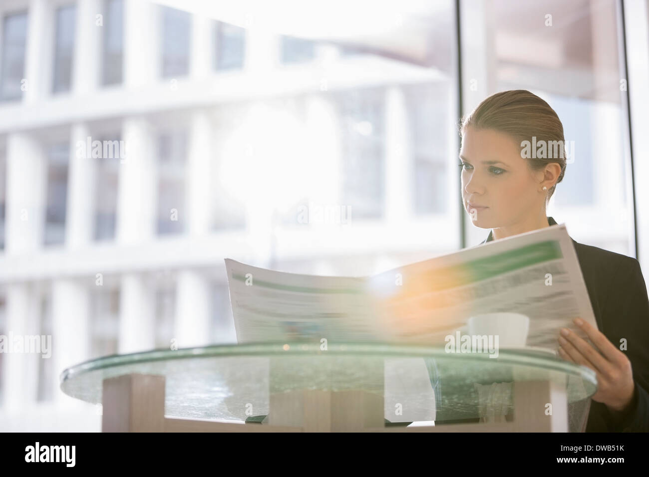Businesswoman reading newspaper at office cafeteria - Stock Image
