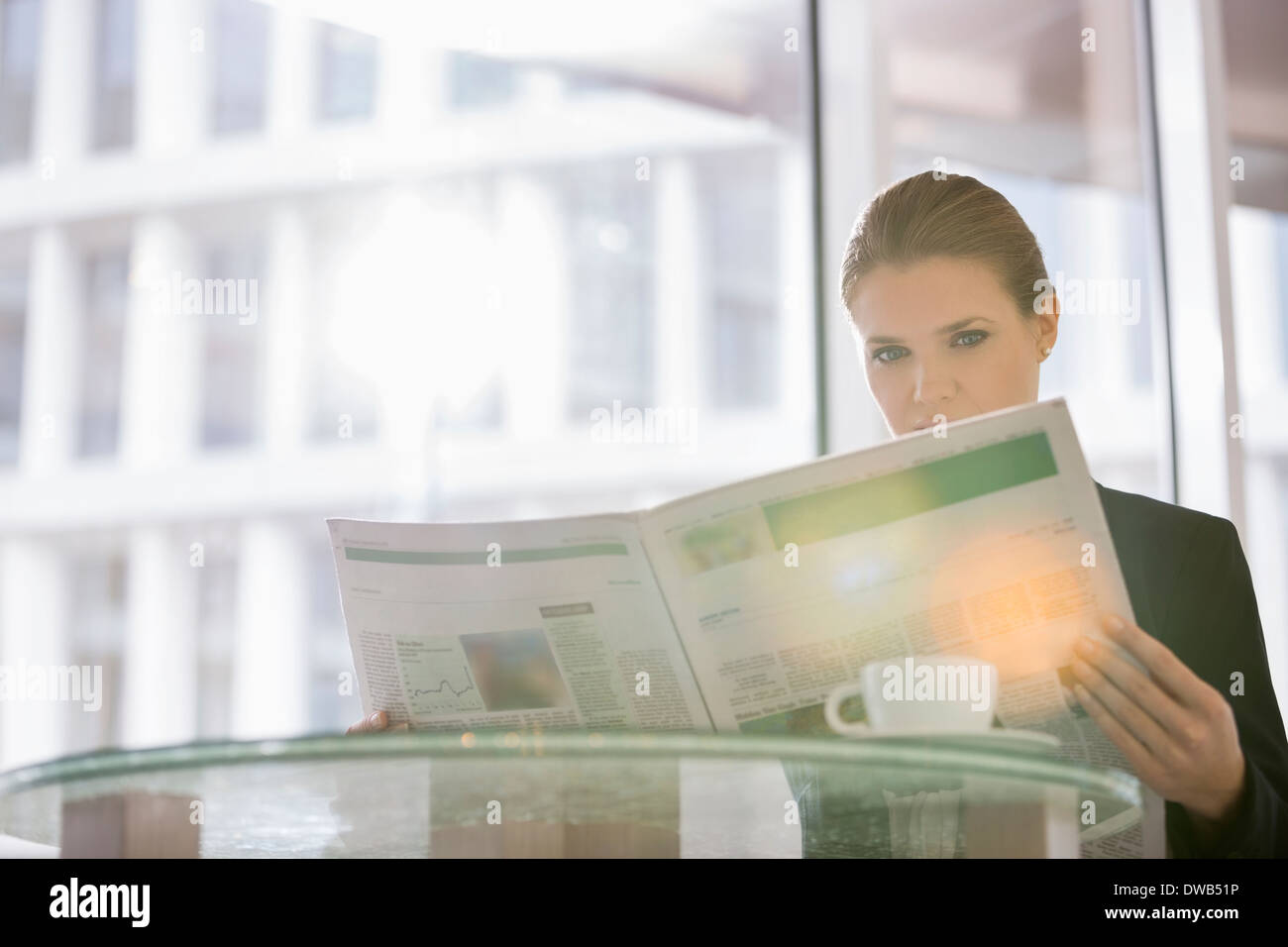 Businesswoman reading newspaper at office cafe - Stock Image