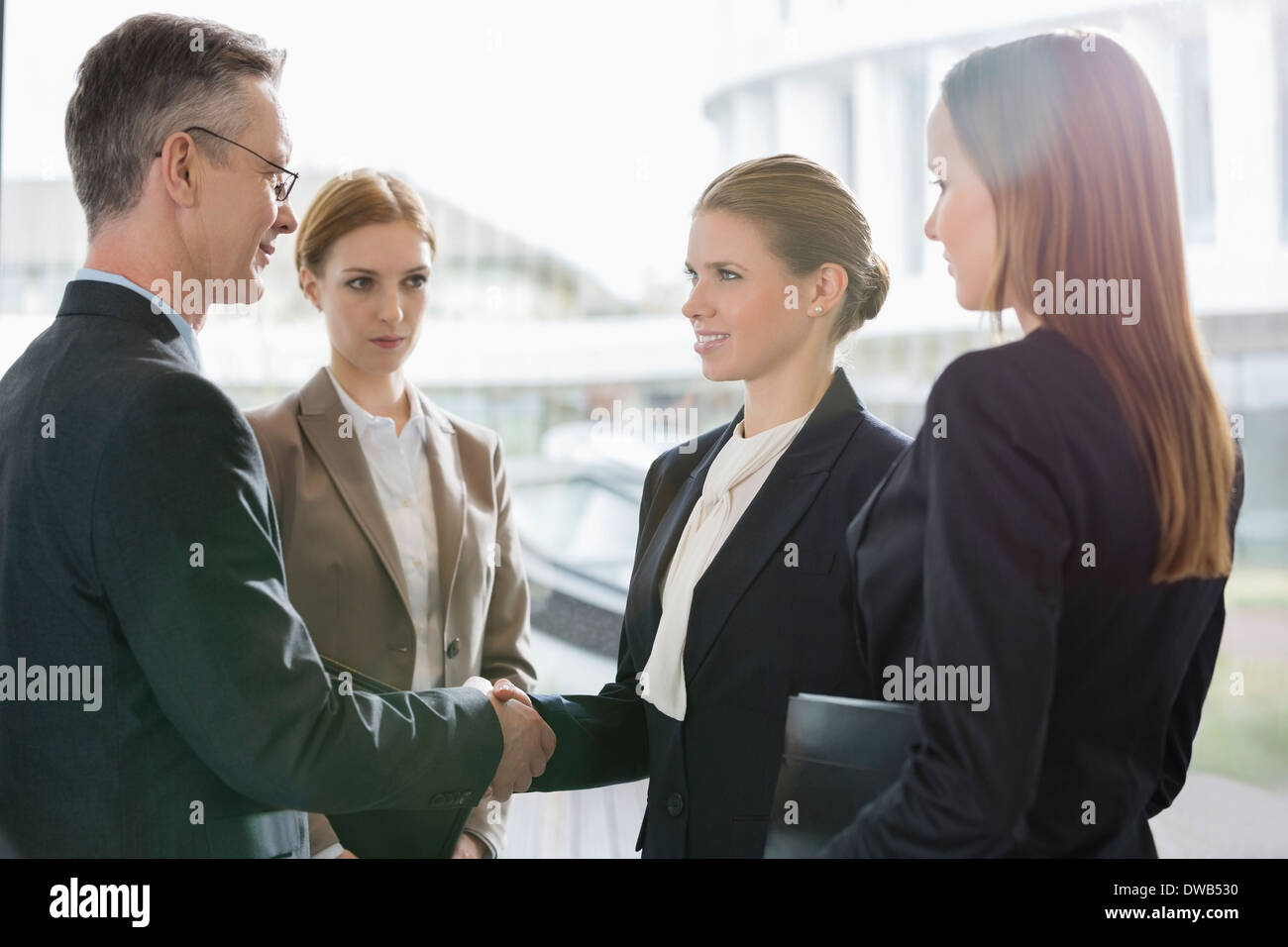 Confident business people shaking hands at workplace - Stock Image