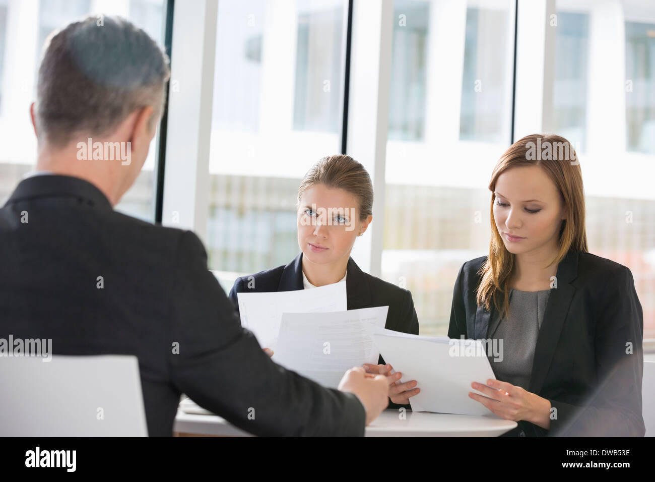 Business people discussing paperwork in office cafeteria Stock Photo
